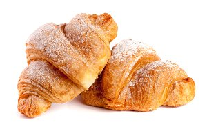 two croissant sprinkled with powdered sugar isolated on a white background closeup
