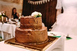 The two-level chocolate wedding cake is decorated with white flowers and stands on the golden stand, on the white table.