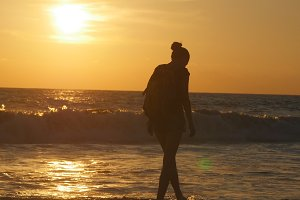 Young female tourist with backpack walking along sea beach at sunset. Beautiful young traveler woman going on ocean shore at sunrise. Girl hiker stepping during travel or summer vacation