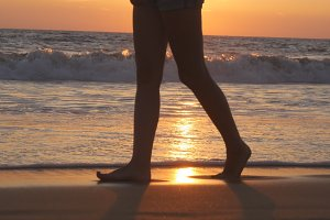 Legs of young woman going along ocean beach during sunrise. Female feet walking barefoot on sea shore at sunset. Girl stepping in shallow water at shoreline. Summer vacation concept. Close up