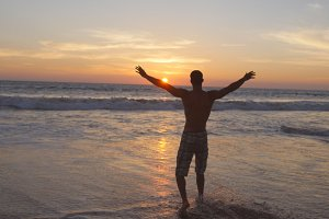 Young man walking at the ocean water on beach at sunset and raised hands. Sporty guy standing at sea shore and relaxing during summer holiday. Vacation concept