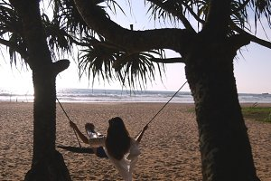 Young happy woman in swimsuit and shirt relaxing at swing at tropical ocean beach. Beautiful girl sitting on swing and enjoying summer vacation or holiday. Female having fun at shore. Rear back view