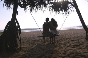 Young romantic couple sitting together on swing at the tropical sea beach and hugging. Pair in love relaxing and kissing on ocean exotic shore during summer vacation. Holiday concept Back rear view