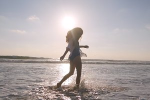 Happy woman walking on the beach of the ocean and spraying the water with her feet. Young beautiful girl enjoying life and having fun at sea shore. Summer vacation. Landscape at background