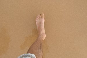 Point of view of young man stepping at the golden sand at sea beach. Male legs walking near ocean. Bare foot of guy going on sandy shore with waves. Summer vacation or holiday Close up POV