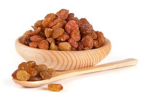 raisins in a wooden bowl with spoon isolated on white background