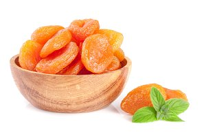Dried apricots in a wooden bowl with mint leaves isolated on white background