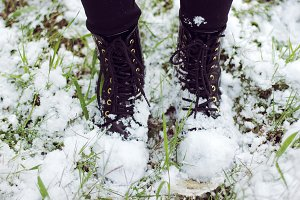 Boots and snow on the green grass