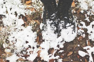 Black boots, dried leafs, snow..