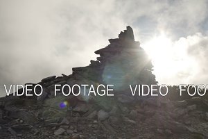 Stack of stones on mountain top on background of rapidly running clouds on sunset. smooth movement