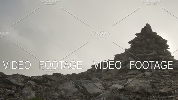 Stack Of Stones On Mountain Top On Background Of Rapidly Running Clouds On Sunset Smooth Movement