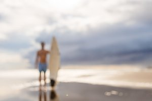 Handsome fit man with surf at beach.