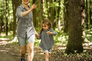 Mother and young daughter walk in the woods