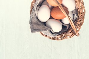 Basket with white and brown natural eggs on white wooden backgro