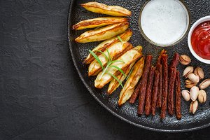 glass of beer and a selection of snacks on cast iron dish