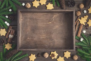 empty rustic tray surrounded by ginger biscuits, fir branches and cones, cinnamon and walnuts. Christmas food background
