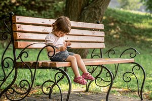 Little girl in the park on the bench with the phone