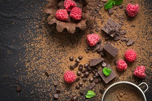 Pieces of chocolate, fresh raspberries and tartlets. Preparation. Food dessert background.