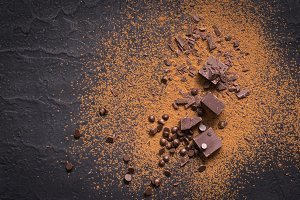 Chocolate background. Pieces and drops of chocolate, cocoa powder on black