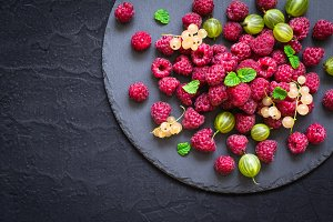 slate dish with different berries. Raspberries, gooseberries, currants on a black background