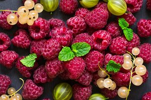 scattering of delicious berries on a black background. Raspberries, currants and gooseberries