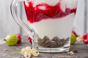 glass with raspberries, granola and yogurt arranged in layers closeup