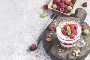 glass with raspberries, granola and yogurt arranged in layers