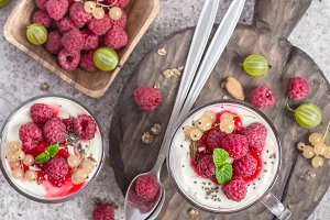 Summer healthy  breakfast with raspberries and yogurt on the cutting board