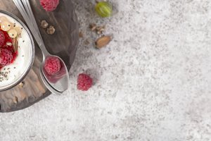 Summer healthy dessert with raspberries and yogurt on the cutting board. Banner format