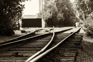 Horizontal black and white sepia railroad track bokeh with peopl