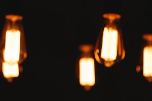 Blurred image of glowing retro light bulbs at night.