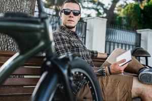 Handsome young guy in sunglasses resting on bench next to bicycle. Person uses a digital tablet while on a walk