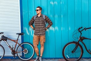 A young male traveler in sunglasses and with a backpack stands along a blue wall with a bicycle
