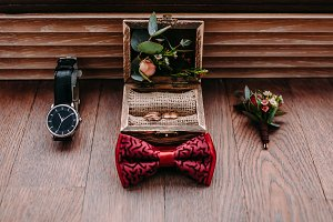 Stylish groom's accessories on a wooden background. Bow tie, boutonniere, and golden rings.