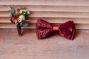 Stylish red bow and boutonniere on wooden background, groom getting ready in morning before the wedding.