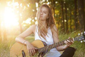 Stylish female with long hair relaxing at sunlight in beautiful forest playing musical instrument with pleasure. Carefree female guitarist having rest playing guitar. Music, hobby, relaxation