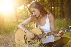 Young girl with luxurious hair dressed in white shirt sitting crossed legs alone at green grass learning playing guitar looking at strings trying to reproduce pleasant melodies. Talented musician