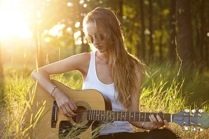 Pretty female with dark long hair feeling relaxed while sitting at green grass in forest playing guitar and singing songs enjoying fresh air. Serious woman wearing sunglasses and casual clothes