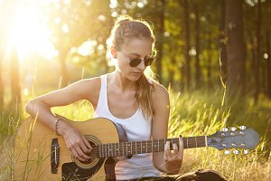 Female musician in stylish eyeglasses and white shirt sitting on green grass playing acoustic guitar and singing songs spending her summer vacations. Talented teenage girl relaxing at green forest