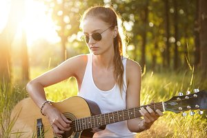 Outdoor portrait of beautiful teenage female with pony tail wearing glasses dressed casually playing guitar while sitting at green grass admiring sunlight. Young model with musical instrument