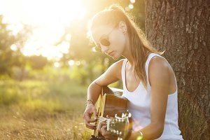Outdoor portrait of young teenage female dressed casually wearing trendy sunglasses playing guitar while sitting near tree in forest. Young female musician playing musical instrument at nature