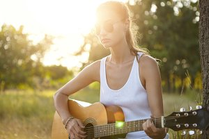 Pretty girl wearing white shirt, sunglasses sitting at green grass with guitar learning how to play enjoying beautiful landscapes of green forest and sunshine. Cute girl in harmony with herself