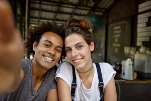 Glad mixed race male with curly hairstyle making photo with his female friend while resting with her at cafeteria. Cheerful interracial friends having fun together making selfie posing in camera