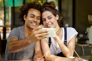 Lovely mixed race couple making selfie while sitting at cafeteria smiling broadly in camera of modern device. Two interracial friends photographing themselves having good mood resting together