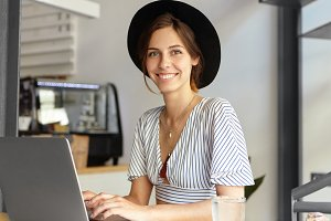 Gorgeous talented woman writer sitting at laptop writing her new book about love looking at camera with smile while typing last page of chapter. Creative female worker in elegant clothes working