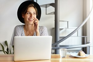 Elegant woman dressed in hat and formal blouse having conversation over smart phone while sitting at her workplace with laptop and lunch looking aside with pleasant smile noticing someone in office