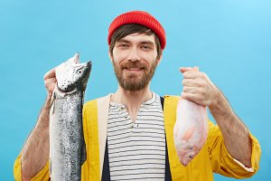 Hobby, recreation, leisure and activity concept. Cheerful unshaven young fisherman or angler in stylish colorful clothing holding two fresh-caught fish, smiling broadly, feeling proud of his catch