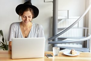 Happy cute businesswoman in white blouse and black hat sitting in office typing necessary documents on her laptop computer smiling while having profits from sales rejoicing her success at work