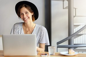Businesswoman dressed officially sitting at her working place using laptop computer having pleasant smile rejoicing end of working day. Caucasian female wearing black hat having rest after work