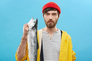 Indoor shot of handsome young European fisherman with beard showing his catch after fishing excursion. Confident male wearing sailor shirt, raincoat and hat posing in studio with big sea fish
